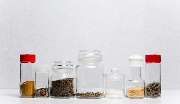 Różne przyprawy w szklanych filiżankach, na białej powierzchni.