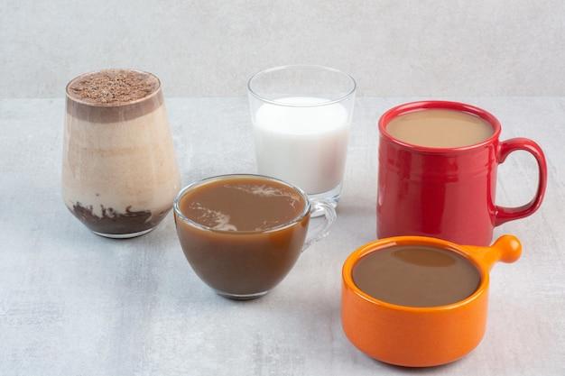 Różne pyszne filiżanki do kawy i mleko na tle kamienia. zdjęcie wysokiej jakości