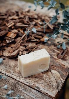 Różne ręcznie robione naturalne mydła na zabytkowym drewnianym stole z dekoracją