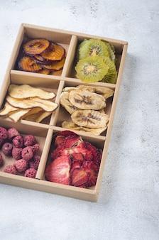 Różne ręcznie suszone frytki w pudełku na szarym tle. koncepcja zdrowego odżywiania, przekąska, bez cukru.