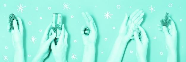 Różne ręki trzyma bożenarodzeniowych elementów zielonego sztandaru tło