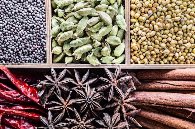 Różne rodzaje całych indyjskich przypraw w drewniane pudełko z bliska widok z góry.