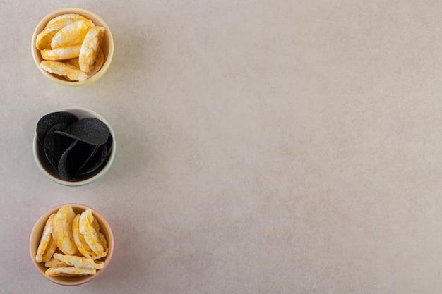 Różne rodzaje chipsów ziemniaczanych na szarej powierzchni