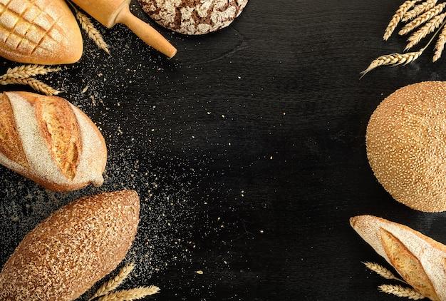 Różne rodzaje chleba na czarnym tle. widok z góry.