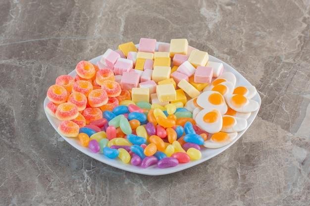 Różne rodzaje cukierków na białym talerzu. kolorowe cukierki.