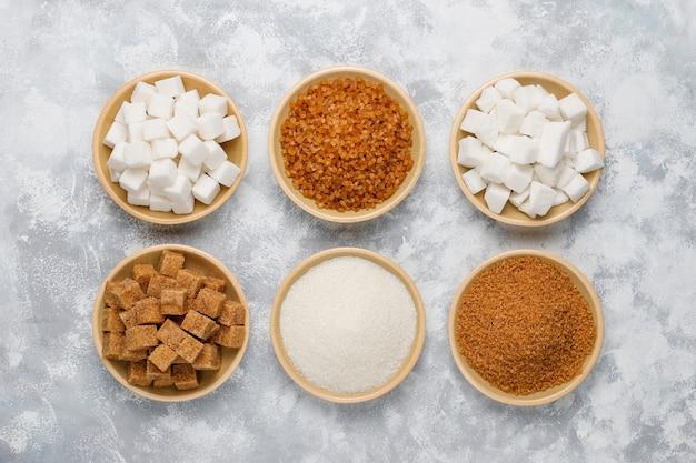 Różne rodzaje cukru, cukru brązowego i białego na betonie, widok z góry