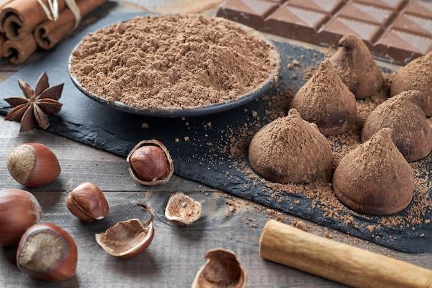 Różne rodzaje czekolady, kakao w proszku, orzechy laskowe i inne przyprawy. składniki do przygotowania domowych trufli.
