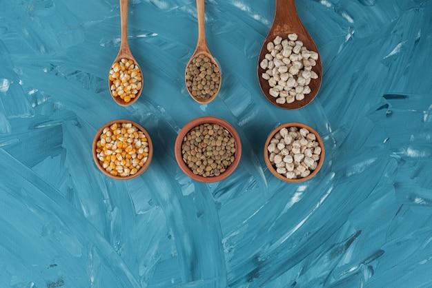 Różne rodzaje fasoli, zbóż, ziaren i soczewicy w drewnianych łyżkach.