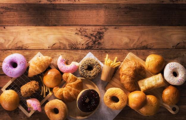 Różne rodzaje fast foodów na drewnianym stole z widokiem z góry z miejscem na kopię