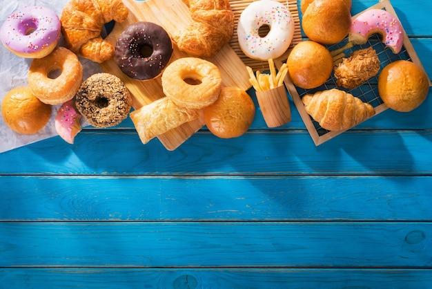 Różne rodzaje fast foodów typu wielokrotnego na niebieskim drewnianym stole z widokiem z góry z miejscem na kopię.