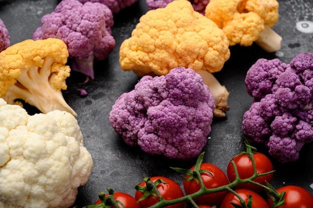 Różne rodzaje kalafiora. fioletowy, żółty i biały zestaw, na czarnym ciemnym tle kamiennego stołu