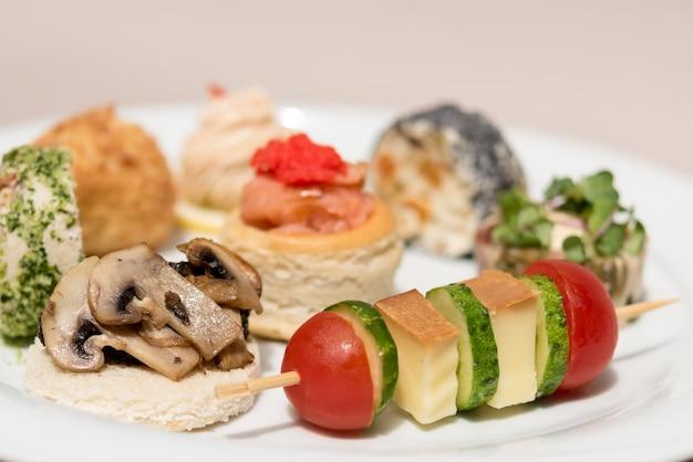 Różne rodzaje kanapek, umieszczonych na białych talerzach, jedzenie na palec