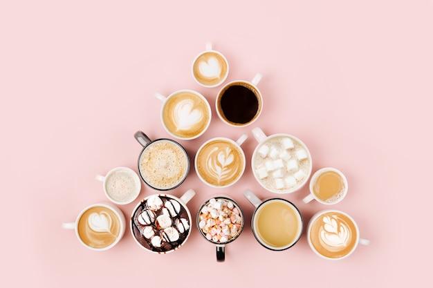 Różne rodzaje kawy w filiżankach różnej wielkości na jasnoróżowym tle. pojęcie czasu kawy. płaski układanie, widok z góry