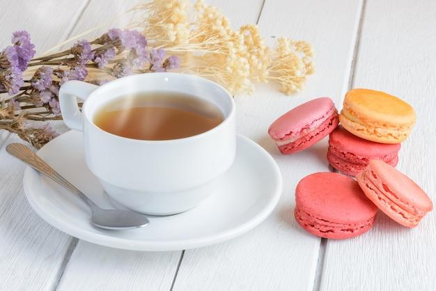 Różne rodzaje kolorów makaroników z filiżanką gorącej herbaty
