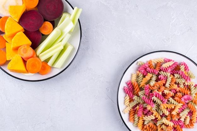 Różne rodzaje kolorowego surowego włoskiego makaronu i jego naturalnych barwników roślinnych: selera, buraków, marchwi, dyni, pasternaku. koncepcja zdrowej żywności