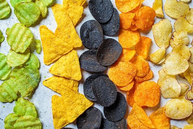 Różne rodzaje kolorowych chipsów ziemniaczanych, szare tło. koncepcja fast food, niezdrowe jedzenie węglowodanów tłustych.
