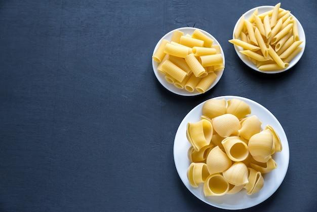 Różne rodzaje makaronów na ciemnym stole
