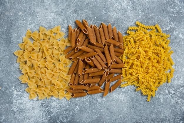 Różne rodzaje makaronów na szaro.