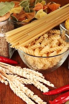 Różne rodzaje makaronów, przypraw, pomidorów na drewnianym stole