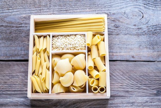 Różne rodzaje makaronów w drewnianym pojemniku