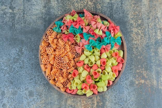 Różne rodzaje makaronów w misce, na marmurowej powierzchni.