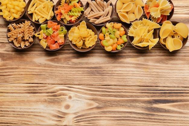 Różne rodzaje makaronów w miskach na drewnianej powierzchni