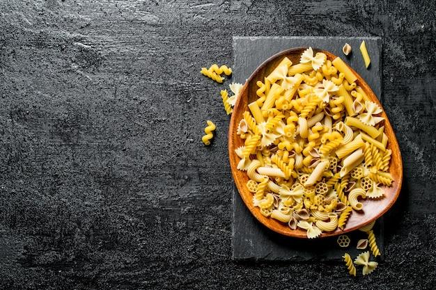 Różne rodzaje makaronów wysychają na talerzu. na czarnym tle rustykalnym