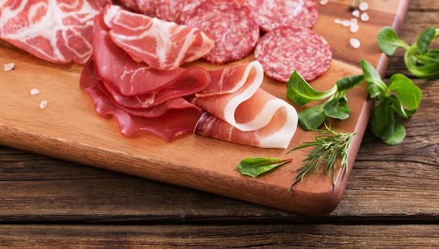 Różne rodzaje mięsa i kiełbas na drewnianym stole
