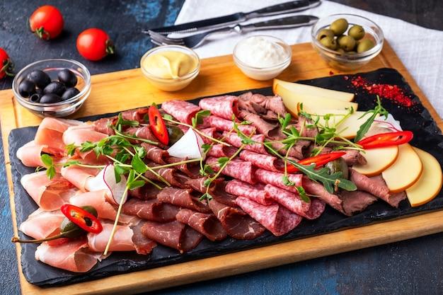 Różne rodzaje mięsa na czarnym kamiennym stole. asortyment szynki, salami, kiełbas i prosciutto.