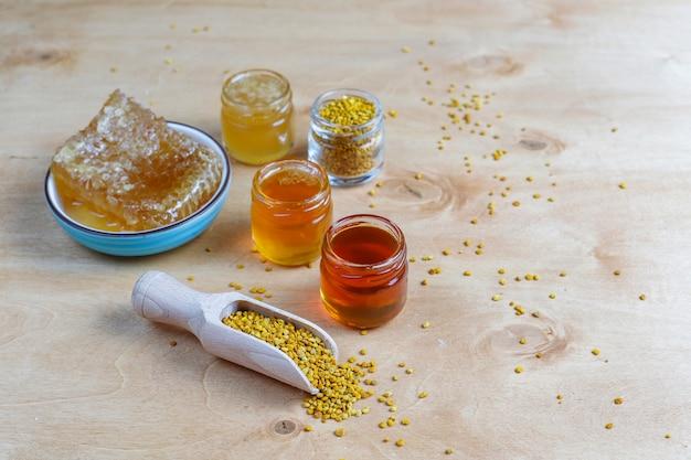Różne rodzaje miodu w szklanych słoikach, plaster miodu i pyłku.