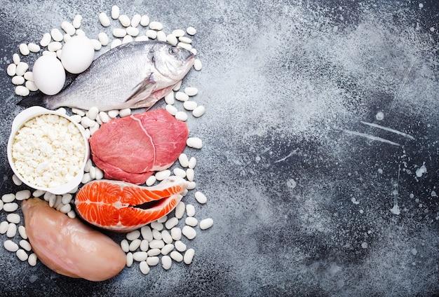 Różne rodzaje naturalnej zdrowej żywności zawierają białko: ryby, mięso, kurczak, jajka, produkty mleczne, fasola na szarym tle rustykalnym, widok z góry, zbliżenie. wolne miejsce na tekst
