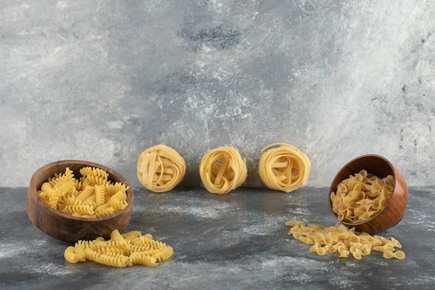 Różne rodzaje niegotowanego makaronu w drewnianych miskach.