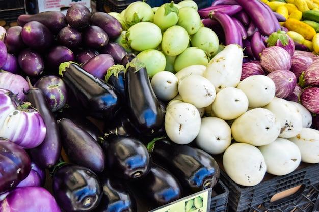 Różne rodzaje oberżyny na rynku organicznym w nowym jorku. produkty z lokalnego rolnictwa.