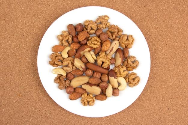 Różne rodzaje orzechów na białym talerzu. zdrowe i białkowe jedzenie