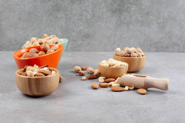 Różne rodzaje orzechów w miseczkach i rozrzucone obok gałki na marmurowej powierzchni.