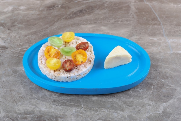 Różne rodzaje owoców na dmuchanych waflach ryżowych na drewnianej tacy, na marmurowej powierzchni