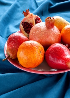 Różne rodzaje owoców na drewnianym stole. gruszki, granaty, pomarańcze, grejpfruty.