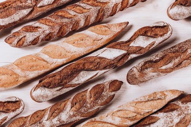 Różne rodzaje pieczywa piekarniczego - świeże rustykalne chrupiący bochenki chleba i bagietki na białym tle.
