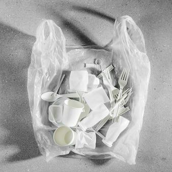 Różne rodzaje plastikowych śmieci w plastikowej torbie. plastikowe opakowania żywności na jasnym tle. pojęcie recyklingu tworzyw sztucznych i ekologii. płaski układanie, widok z góry