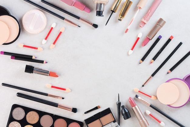 Różne rodzaje produktów do makijażu na szaro.