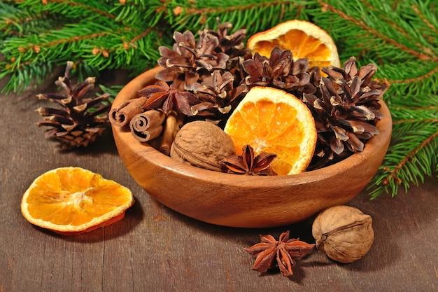 Różne rodzaje przypraw, orzechy, suszone pomarańcze i szyszki w misce i gałęzi spruse