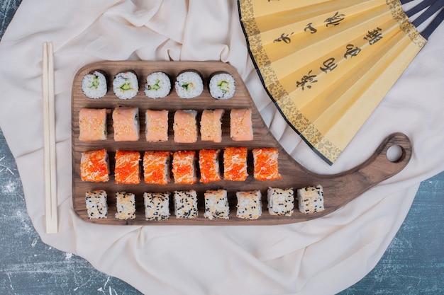Różne rodzaje rolad sushi podawane na drewnianym talerzu z pałeczkami i japońskim wachlarzem.