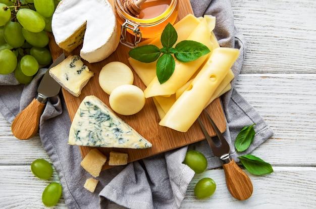 Różne rodzaje sera na białym drewnianym stole