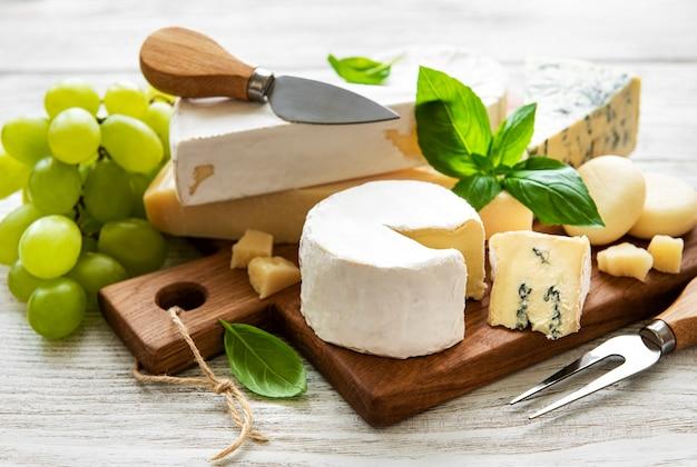 Różne rodzaje sera na białym tle drewnianych