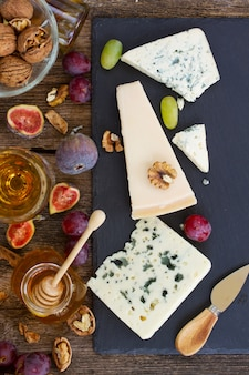 Różne rodzaje sera na czarnej desce do krojenia, widok z góry