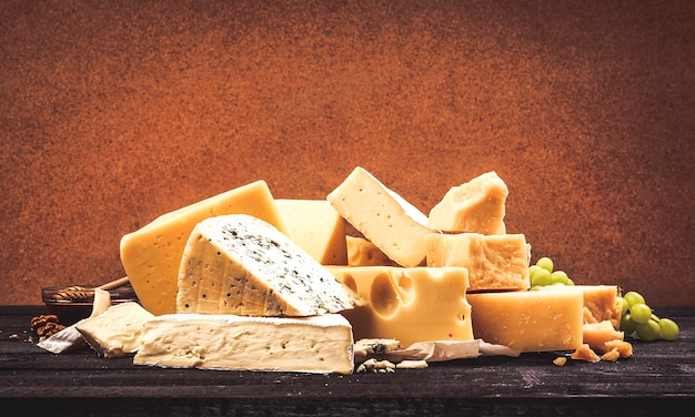 Różne rodzaje sera na czarnym drewnianym stole