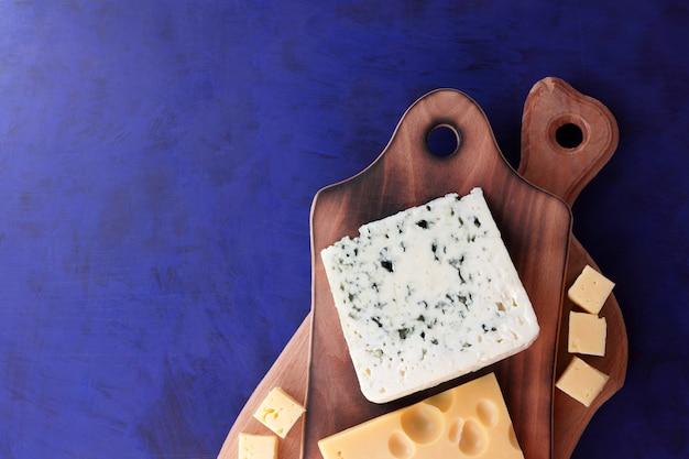 Różne rodzaje sera na drewnianej desce. twardy ser na niebieskim tle. nabiał