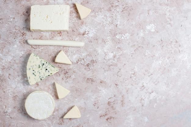 Różne rodzaje sera na jasnobrązowej powierzchni