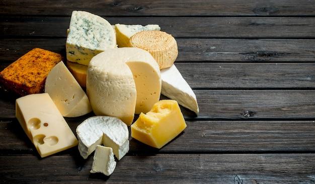 Różne rodzaje sera na rustykalnym stole.