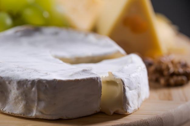 Różne rodzaje sera na talerzu z winogronami i orzechami
